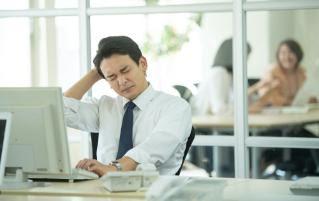 コンピューターの前で頭を悩ませている男性