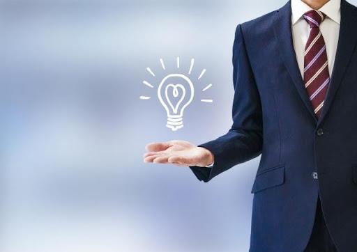 ビジネスマンの手に浮かぶ電球マーク