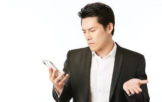 携帯を片手に悩む人